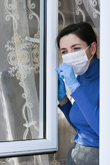 A girl in quarantine with a mask looks out the window at home - infection and spread of the new coronavirus 2019. teenage girl looking through window with mask.