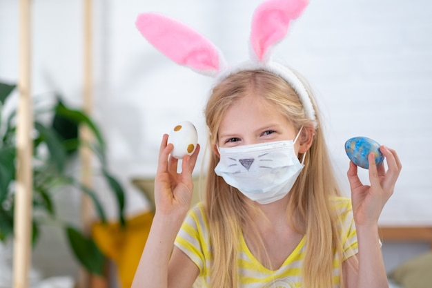 Girl in rabbit bunny ears on head and protective mask with colored eggs at home