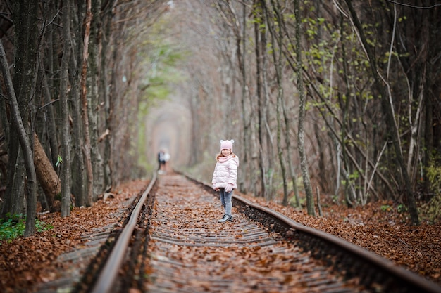 Girl in railway green tunnel. love tunnel in autumn. railway and tunnel from trees