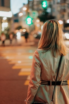 Girl in a raincoat walks through the city back view. town