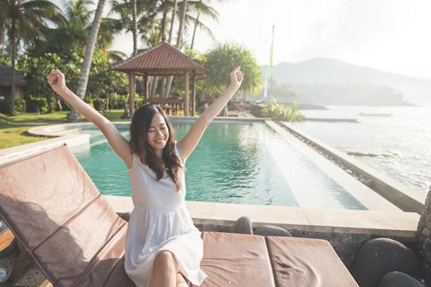 Girl raise her hands enjoying sunlight on tropical beach