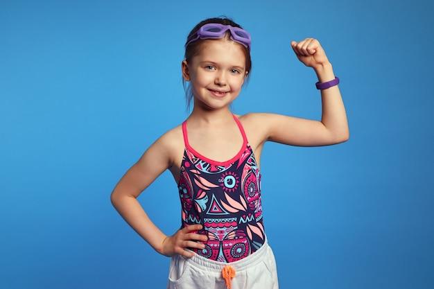 Девушка поднимает руку и показывает мышцы, готовые к плаванию, в очках и купальнике