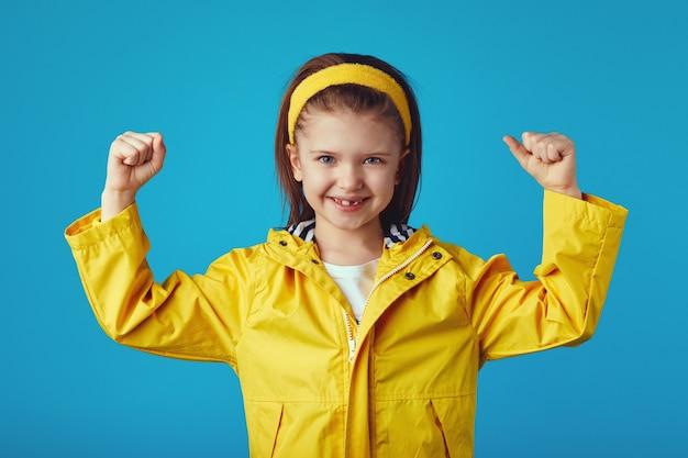 Девушка поднимает руки и показывает мышцы, одетые в желтый плащ и повязку на голову