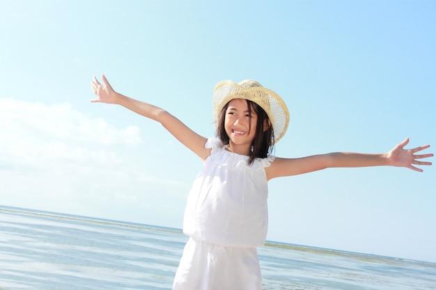 女の子は青い空を背景に彼女の手を発生させます
