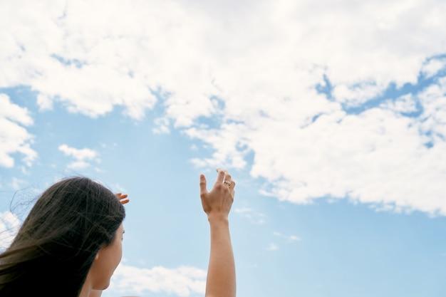 Girl raises her hands to the sky praying to god closeup
