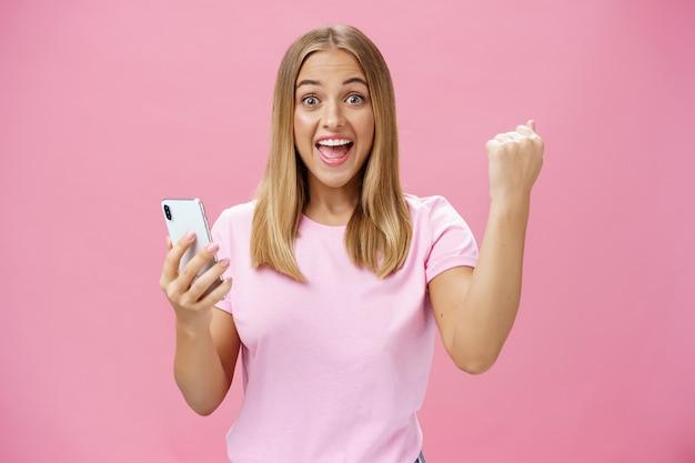 携帯電話を持って歓声と勝利でくいしばられた握りこぶしを上げて、ピンクの背景の上の楽しいジェスチャーで祝うカメラで興奮して幸せに笑う女の子