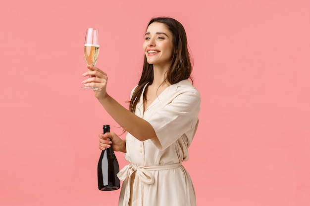 Girl raising glass for friend, give a toast looking left at person, holding champagne and smiling joyfully,celebrating special occasion