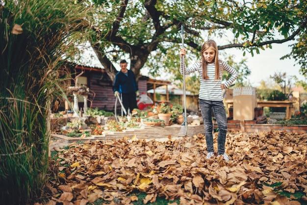 Girl raking up autumn leaves