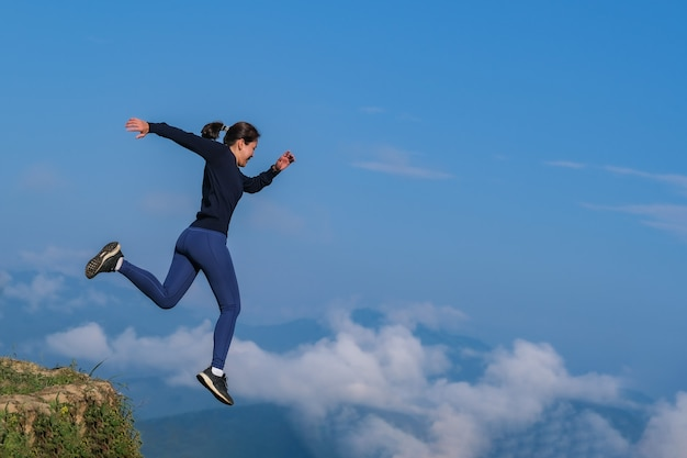 The girl ran, jumped from a high place, and ran in a mountainous field.