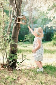 소녀는 공원에서 조류 피더에 도달합니다. 고품질 사진