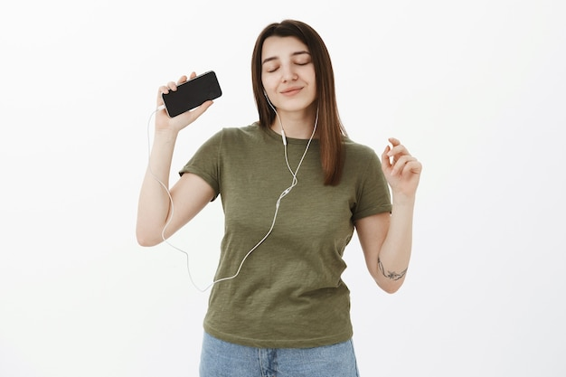 Girl reaching nirvana and positive emotions, having positive vibes from awesome sound of earphones, listening music dancing sensually with closed eyes and happy smile, raising hand with smartphone