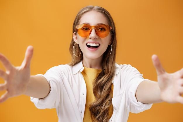 카메라에 손을 뻗은 소녀는 넓은 미소와 오렌지 배경 위에 즐겁고 행복한 포즈를 취하는 신제품을 손에 들고 싶어하는 흥분된 열망하는 표정으로 기대하는 것을 껴안거나 잡으려고 합니다.