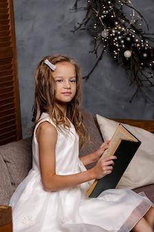 소녀는 크리스마스 트리 장식 된 거실에서 책을 읽고