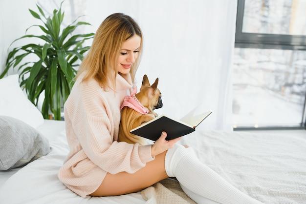 Девушка читает книгу. милая девушка читает книгу со своей собакой дома. довольно стильная девушка.