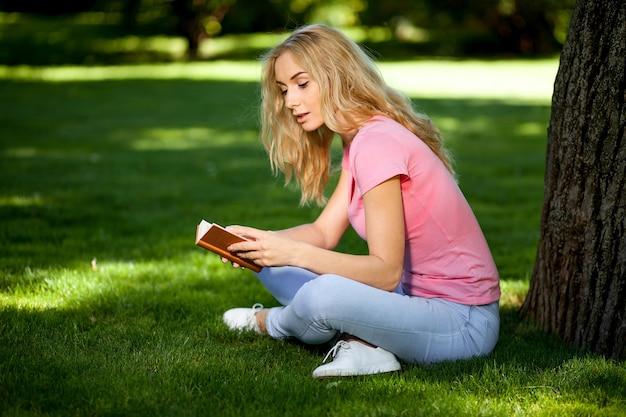 木の下の芝生の公園で本を読んでいる女の子。