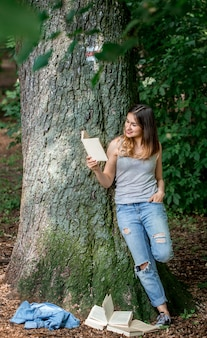 Девушка читает книгу возле дерева в парке