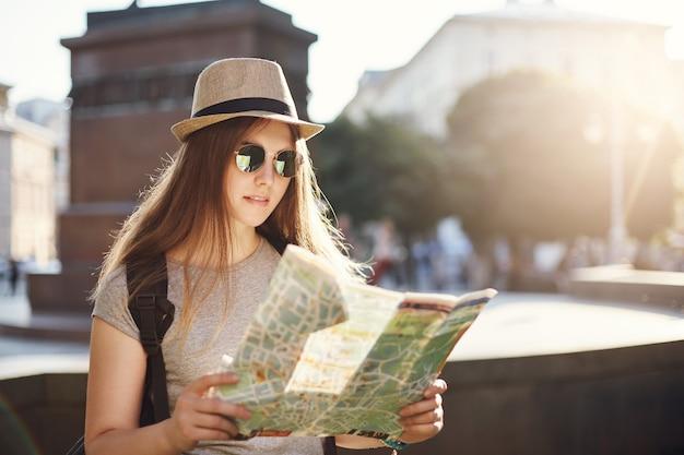 帽子をかぶってヨーロッパの都市に座って、世界を旅する地図を読んでいる女の子。大きな投資を観光する。