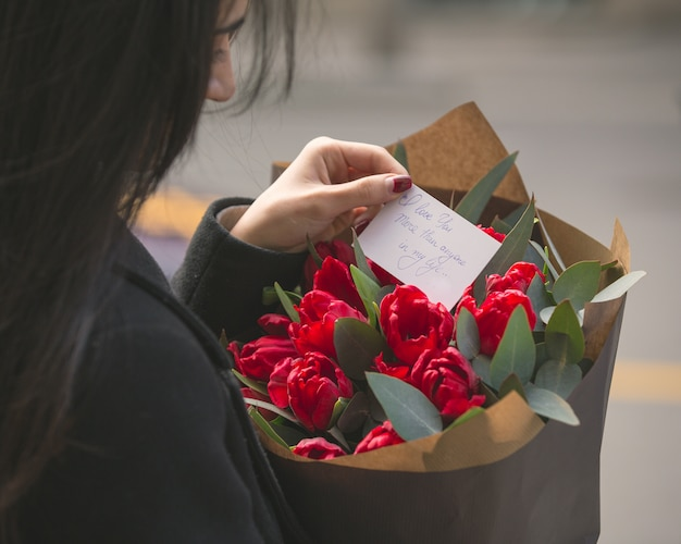 빨간 튤립 꽃다발에 넣어 메모를 읽는 여자