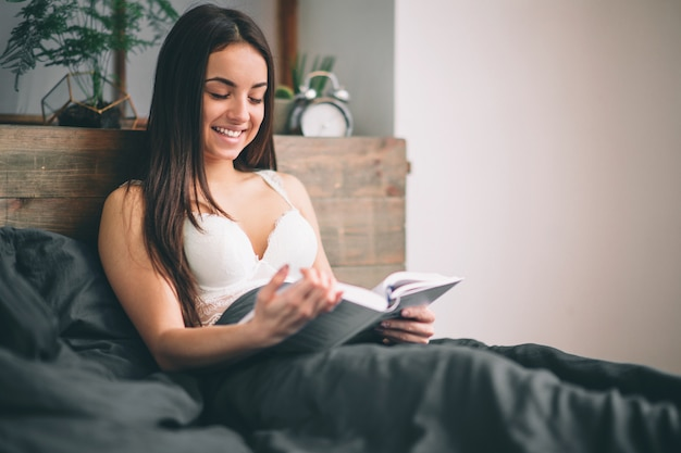 本を読んで、ベッドでコーヒーを飲む女の子