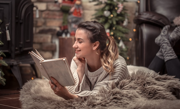 Girl reading a book in a cozy home atmosphere near the fireplace