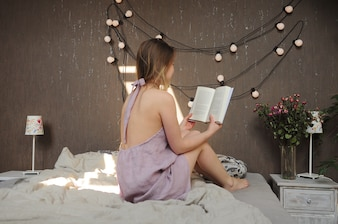 Girl reading book in bed in pajamas