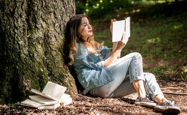 Girl reading a book near a tree