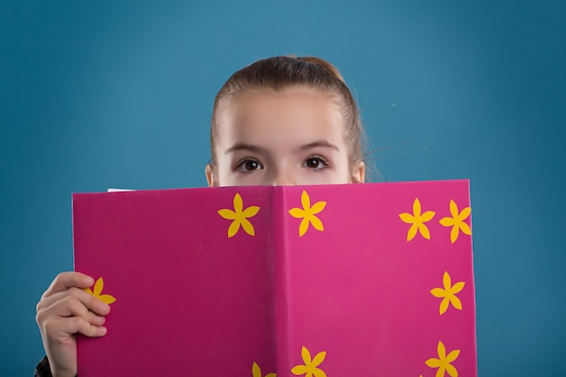 Girl reading a book in a pink cover, shooting in the studio