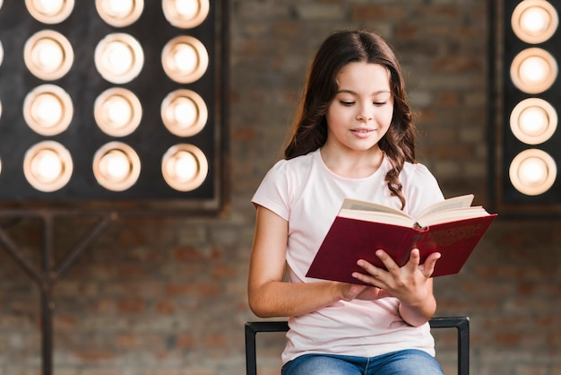 Girl reading book sitting against stage light