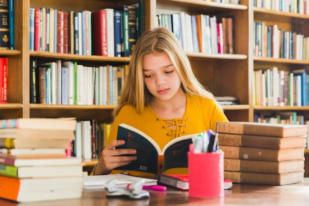 Girl reading book sitting in library