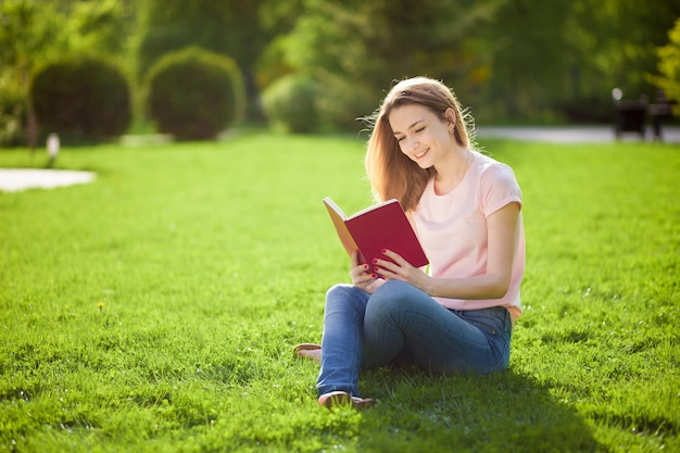 Девушка, читающая книгу, сидя на траве