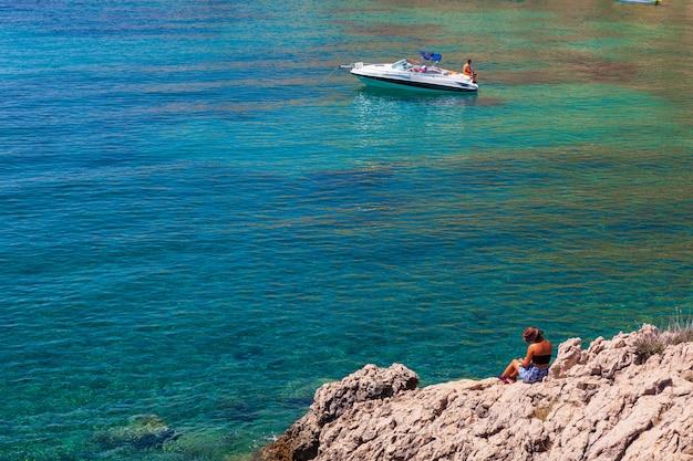 Girl reading a book sitting on the rock next to the sea. stara baska, croatia