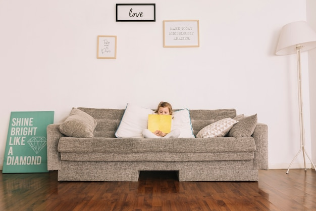 Girl reading book on soft couch