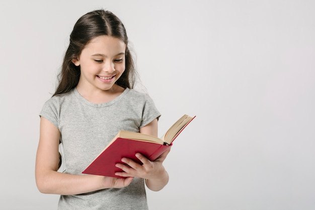 Girl reading book in studio and smiling