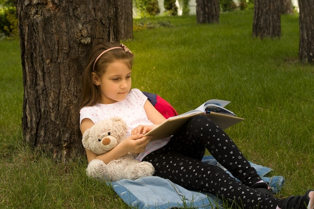 Girl reading a book under a tree on the green grass. summer vacation, picnic in nature