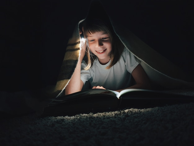 Girl reading a book with a flashlight