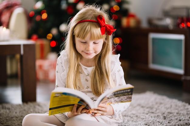 크리스마스 트리 앞에서 읽는 여자