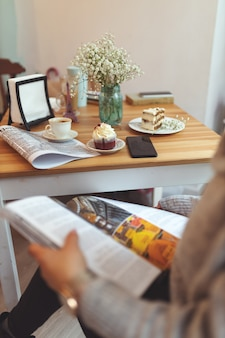 Girl reading a magazine in front of a table with different desserts