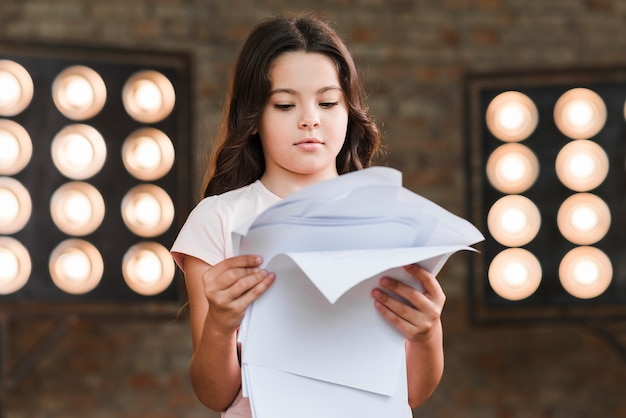 Girl reading scripts in front of stage light