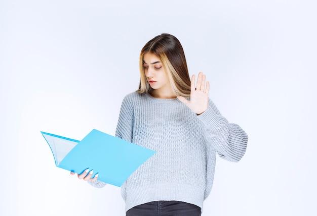 파란색 폴더에 대한 보고서를 읽고 발언하는 소녀.