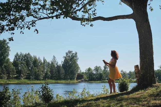 Девушка читает книгу у озера. обучение за городом.
