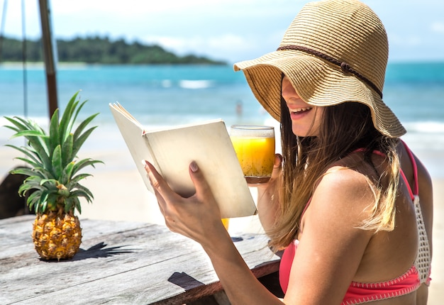 Girl reads a book by the sea