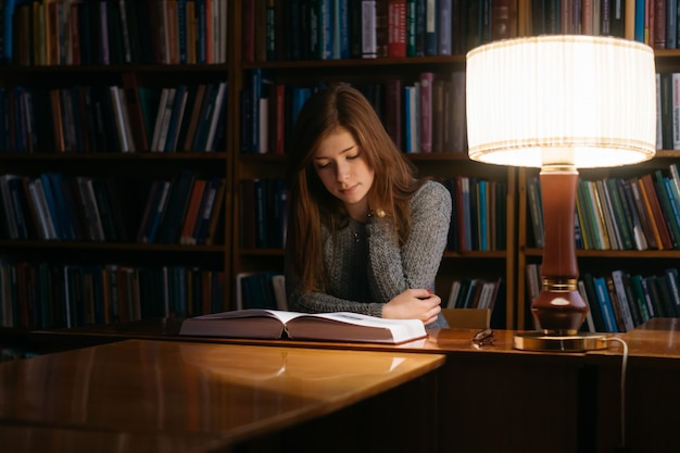 A girl reads a book in a library while sitting at a table