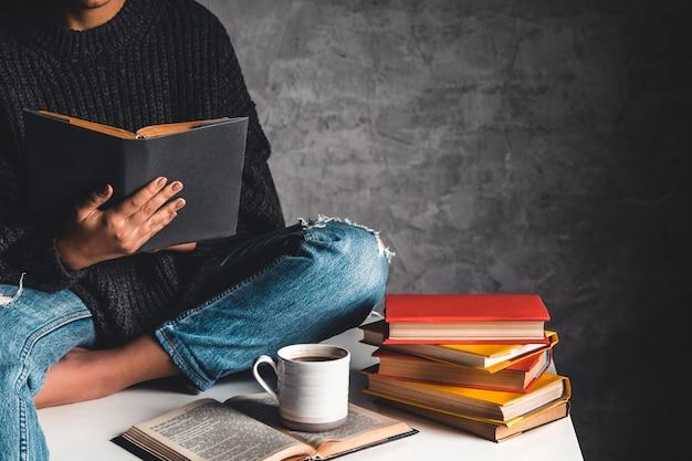 Девушка читает книги, учится, развивается с чашкой кофе на белом столе и сером фоне.