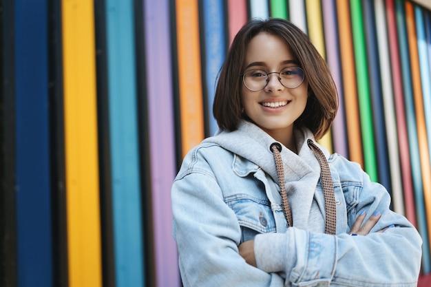 アクションの準備ができている女の子。短い髪、メガネ、デニムジャケット、春の天気を楽しんで、街の通りを歩いて、自信を持って両手を胸に抱き、虹の壁の近くで笑っている愛らしい若い女性。