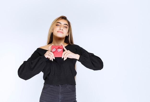 La ragazza ha ricevuto una confezione regalo rossa e si sentiva felice. foto di alta qualità