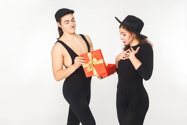 Девушка получает подарок на день рождения от молодого взрослого мужчины. студия выстрел, изолированные на белом фоне