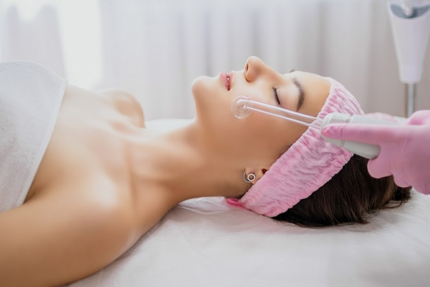Girl receiving darsonval procedure electric massage at beauty salon