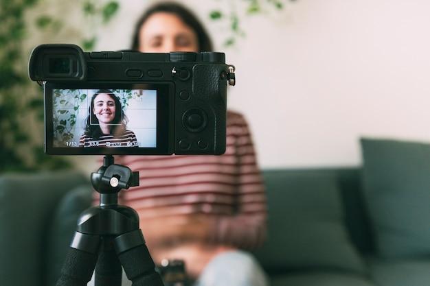 집에서 카메라로 자신을 녹화하는 소녀. 카메라에 선택적 초점입니다. 비디오 블로깅 개념