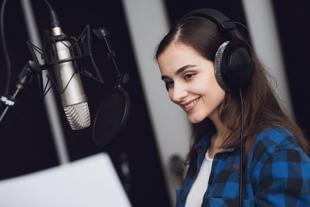 The girl in the recording studio sings a song.