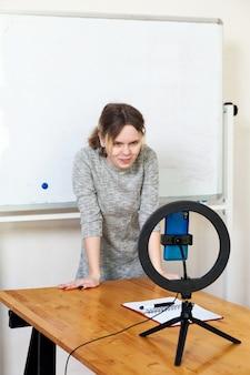 Девушка записывает видео на смартфон и освещает себя кольцевой лампой